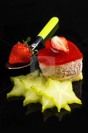 Heart strawberry cake stock photo, Heart shaped strawberry cake dith star fruit or carambola decoration over black reflective backgound by Francesco Perre