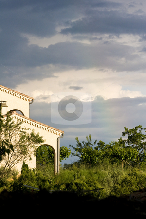 Rainbow and stormy sky over a sunlit house stock photo, Rainbow and stormy sky over a sunlit house by Mark Yuill