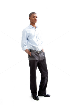 Young business man stock photo, Young African business man standing relaxed and secure with hands in pocket, isolated by Paul Hakimata
