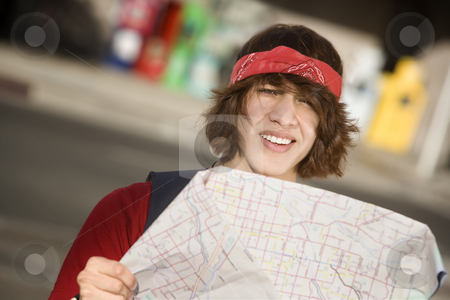 Young Man with a Map stock photo, Lost Young Man on the Sidewalk with Map by Scott Griessel