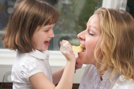 Daughter Feeding Mom an Apple stock photo, Daughter Having Fun Feeding Mom an Apple Slice by Andy Dean