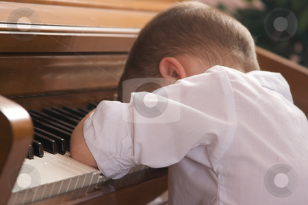 Young Boy with Head on the Piano stock photo, Sad Young Boy with Head on the Piano by Andy Dean