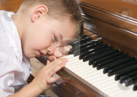 Young Boy Playing the Piano stock photo, Young Boy with Head on Hand Playing the Piano by Andy Dean