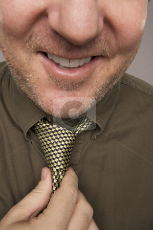 Smiling Man Fixing Tie stock photo, Smiling Man Fixing Tie Against Grey Background by Andy Dean