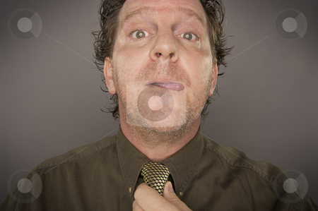 Man Concentrating Fixing Tie stock photo, Man Concentrating Fixing Tie on a Grey Background by Andy Dean