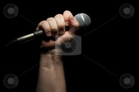 Microphone in Fist stock photo, Microphone clinched firmly in male fist on a black background. by Andy Dean