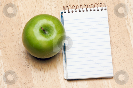 Pad of Paper and Apple on Wood stock photo, Pad of Paper and Apple on a Wood Background by Andy Dean