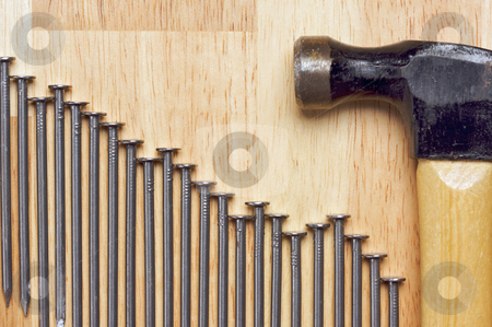 Hammer and Nails Abstract stock photo, Hammer and Declining Graph of Nails Abstract on Wood Background. by Andy Dean