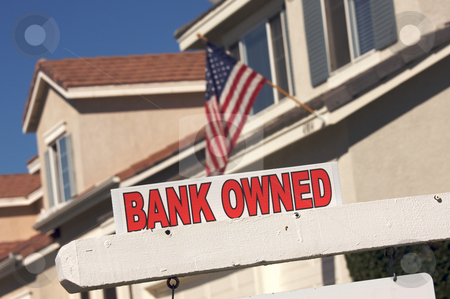 Bank Owned Real Estate Sign and House with American Flag stock photo, Bank Owned Real Estate Sign and House with American Flag in the Background. by Andy Dean