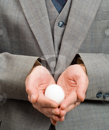 New Hope stock photo, Closeup of a white egg in the hands of a businessman, symbolizing new hope or a new beginning by Richard Nelson