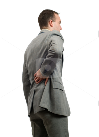 Back Pain stock photo, A young businessman holding his back in pain, isolated against a white background by Richard Nelson