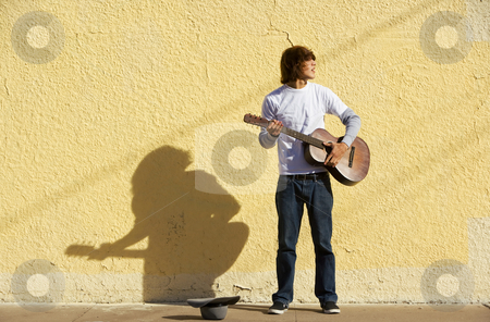 Musician on Sidewalk stock photo, Young male musician alone on the sidewalk with guitar by Scott Griessel