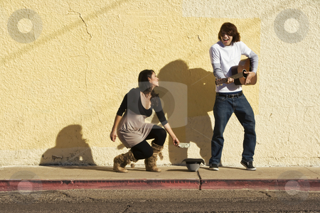 Musician on Sidewalk and Woman Pedestrian stock photo, Musician on Sidewalk and Woman Pedestrian by Scott Griessel