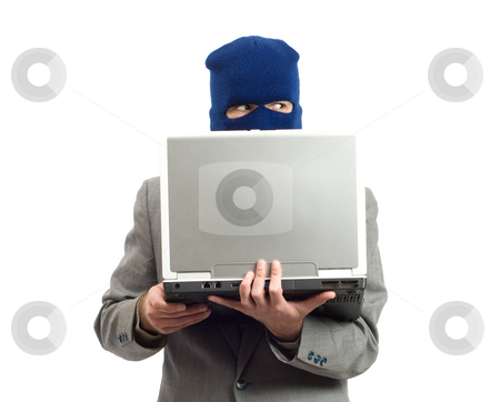Identity Theft stock photo, A businessman wearing a mask using a laptop computer to change his identity by Richard Nelson