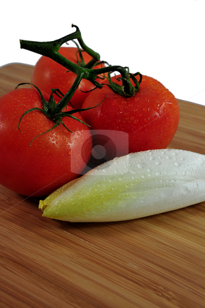 Tomato And Endive stock photo, Thre tomatoes and Endive on a wooden cutting board. by Lynn Bendickson