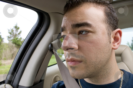 Bored Car Passenger stock photo, This young man looks bored and stares out the window while riding as a passenger on a long road trip. by Todd Arena