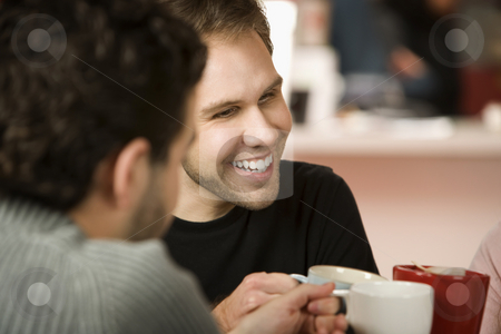 Young Man Toasting with Coffee Cups stock photo, Young man toasting friends with coffee cups by Scott Griessel