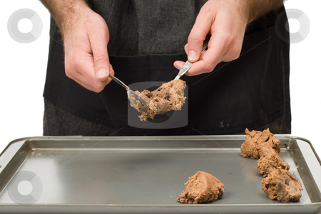 Dropping Cookie stock photo, A man dropping chocolate dough onto a cookie sheet by Richard Nelson