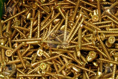Screws stock photo, The heap of screws lays on a surface by Joanna Szycik