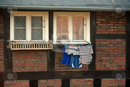 Laundry hanging at the window stock photo, Laundry hanging at the window in old building by Joanna Szycik
