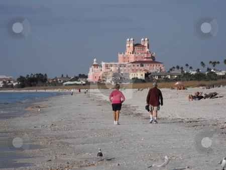 St. Pete's Pink Palace stock photo, A pair of senior citizen's walk along the shore of Florida's St. Pete's Beach toward the historic Pink Palace shown in the background.  The Don Cesar Beach Resort on the Gulf coast  has been known as the Pink Palace since 1928. by Dennis Thomsen
