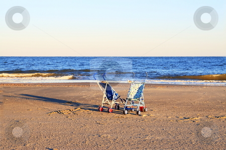 Strollers  stock photo, Two lone strollers on the beach parked sisde by side by Jack Schiffer