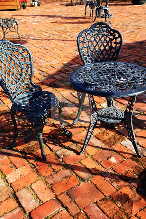 Iron  & coblestone stock photo, Cast iron seating at old historic savannah georgia sidewalk cafe by Jack Schiffer