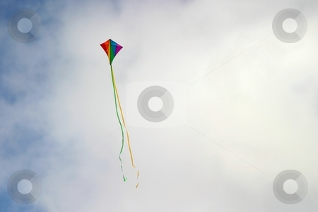 Kite stock photo, Kite up in the sky with clouds in the background. by Henrik Lehnerer