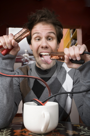 Coffee Jolt stock photo, Young man holding jumper cables coming out of coffee mug by Scott Griessel