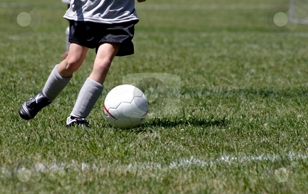 Playing Soccer stock photo, A young person dribbling a soccer ball down the field. by Karma Shuford