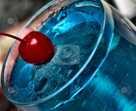 Red Splash stock photo, A red cherry splashing into a glass of blue water by Karma Shuford