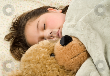 Sleepy Child stock photo, Young girl snuggling with a stuffed bear, covered in a warm blanket by Richard Nelson