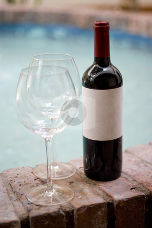 Red Wine and Glasses stock photo, A red wine bottle and two empty glasses by the pool.  Plenty of copy space on the blank wine label. by Todd Arena