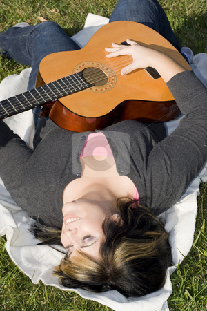 Girl With a Guitar stock photo, A young hispanic woman playing a guitar while laying on a blanket in the green grass.  Her hair is highlighted with blonde streaks. by Todd Arena
