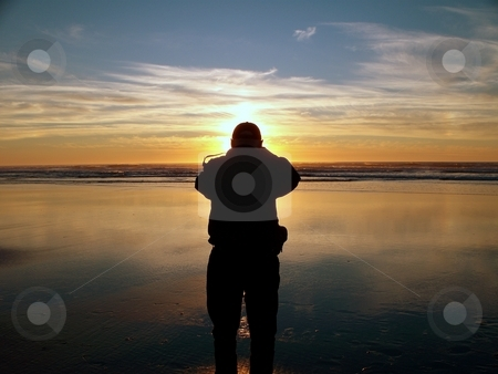 Saving a Sunset stock photo, Man on the beach taking pictures by Carol Grimes