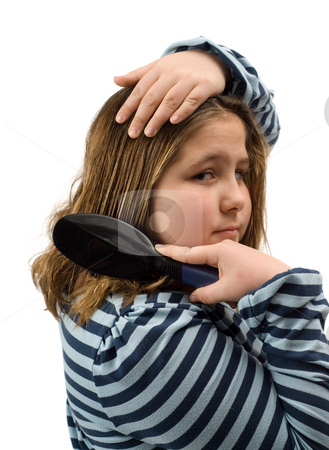 Girl Brushing Her Hair stock photo, A young girl brushing her own hair, isolated against a white background by Richard Nelson
