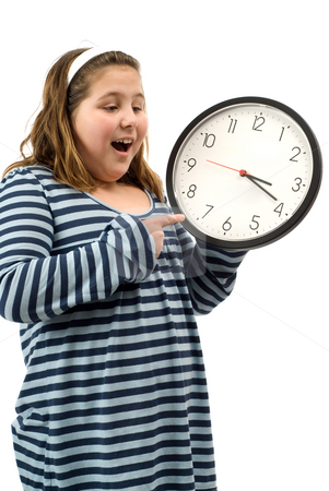 Home Time stock photo, A young girl looking happy as she points to a clock that says it is almost time to go home by Richard Nelson