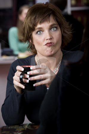 Woman with Friend in Coffee House stock photo, Pretty woman with coffee and funny expression by Scott Griessel