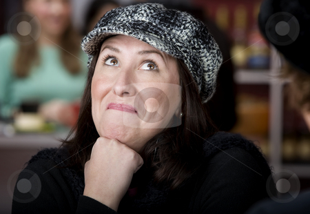 Hispanic woman with coffee stock photo, Pretty Hispanic woman in hat with funny expression by Scott Griessel