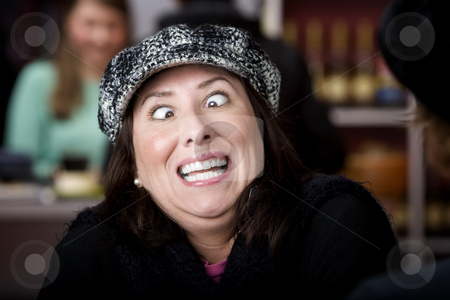 Hispanic woman with funny expression stock photo, Hispanic woman in hat crossing her eyes by Scott Griessel