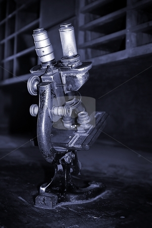 Old Microscope stock photo, Aged microscope standing on an old wooden secretary. by Henrik Lehnerer