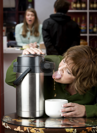 Woman drinking coffee directly from a dispenser stock photo, Woman drinking coffee directly from a beverage dispenser by Scott Griessel