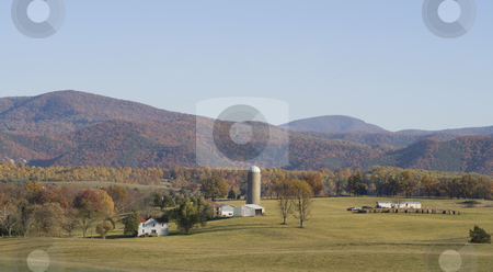 Autumn countryside stock photo, Beautiful countryside with colorful fall foliage and distant mountains. by Robert Ranson