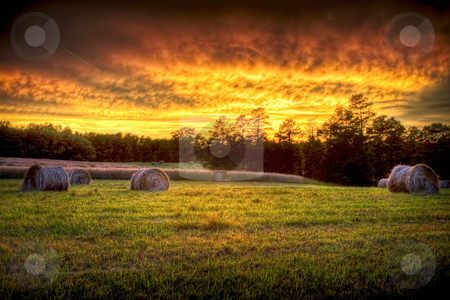 Sunset field scenery with hay rounds stock photo, Beautiful sunset lighting a field with hay rounds producing brilliant and amazing colors. by Robert Ranson