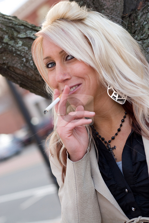 Smoking a Cigarette stock photo, A young blonde woman takes a cigarette break outdoors. by Todd Arena