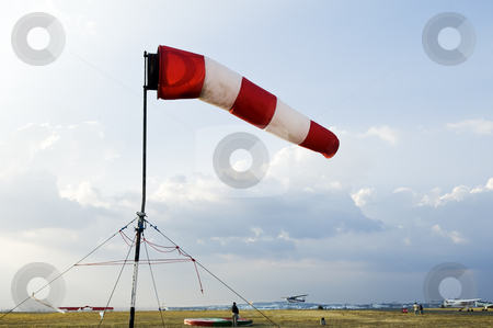 Windsock stock photo, A red and white windsock flying in the wind to signal direction on an airfield by Manuel Ribeiro