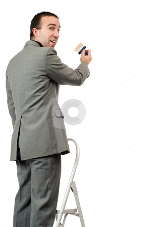 Painting Businessman stock photo, A young businessman standing on a ladder and painting something, isolated against a white background by Richard Nelson