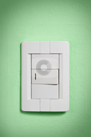 White light switch on green wall. stock photo, White light switch against a green wall. by Pablo Caridad