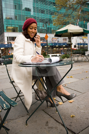 Business Woman In The City stock photo, An attractive business woman talking on her cell phone while sitting at a table outdoors. by Todd Arena
