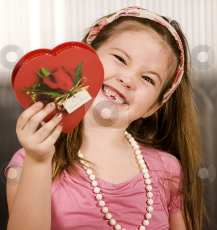 Cute young girl with Valentine stock photo, Cute little girl with a Valentine and funny expression by Scott Griessel